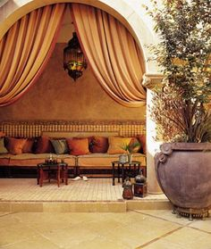 Outdoor Moroccan living space. The curtains, the lantern, the giant purple garden pot, all these elements make this beautiful space stand out! #Moroccan #Outdoor #Decor.