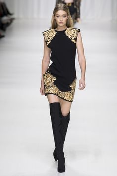 Gigi Hadid storms the runway at Versace's SS18 Show in a black and gold sleeveless dress & classic OTK boots #tunup...x