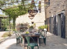 Metal pergola attached to wall of stone house; France?