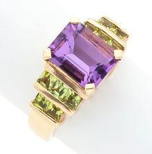 The ring features an emerald-cut amethyst measuring approximately 1.00 x 8.00 x 5.30 and weighing approximately 2.50 carats, enhanced by square-cut peridots weighing a total of approximately 1.00 carat, set in 14k gold. Gross weight 6.60 grams.