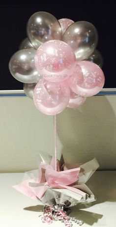 Light pink happy birthday balloons and silver Pearl balloons made into a balloon topiary for a table centerpiece.