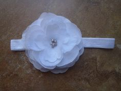 """White silk flower adorned with 5 rhinestones in the middle on a 5/8"""" white satin elastic. Perfect for everyday or special occasion."""