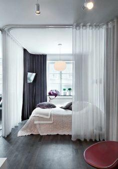 Cloisonner avec des rideaux : les rails fixés au plafond permettent d'installer des rideaux qui suivent le trajet que l'on désire