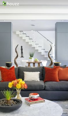 Gray And Orange Living Room Features Walls Of Undressed Windows Lined With  A Gray Sectional Sofa Adorned With Gray And Orange Pillows Facing A Whitu2026