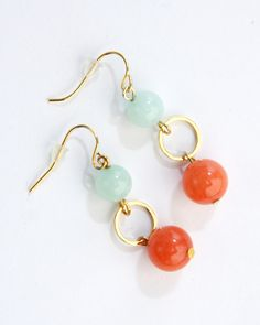 Vi Bella Jewelry - Peek-A-Boo Earrings - Who doesn't love a good game of Peek-A-Boo? The aptly named Peek-A-Boo Earrings give any outfit just the right pop of color! They feature natural white jade beads dyed soft light blue-green and coral-orange connected by small gold hoops. Pair with the Peek-A-Boo Necklace.     Length:  1.5 Inches     Handcrafted by Vi Bella Artists in Haiti  $14.95