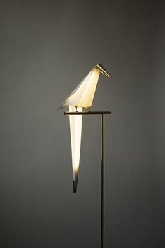 CouleurPerch Light - Umut Yamac. The stylized bird-shaped light sits still on its perch until you pass it, or a draft sets it in motion: then the bird gracefully swings, dipping back and forth whilst staying illuminated.