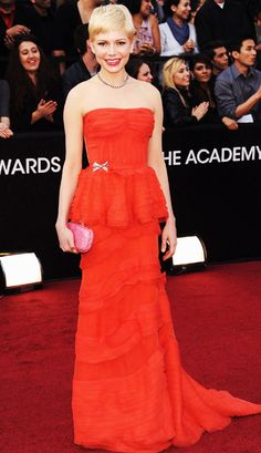 """Michelle Williams in a poppy orange strapless Louis Vuitton dress with peplum detail. She paired her Oscars dress with a Fred Leighton for Forevermark necklace and a pink Bottega Veneta """"Blush Crocodile Knot"""" clutch."""