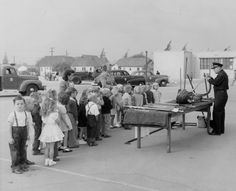 Burbank School children lined up to watch a fire fighter demonstrating equipment during Fire Prevention week, circa 1940s.  Burbank Historical Society. San Fernando Valley History Digital Library.