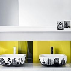 A bright yellow splashback makes a feature out of these statement basins. For a designer look at lower cost, a panel of Perspex has been painted to create the splashback.