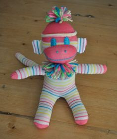 Sock Monkey Baby in Pink and Pastel Rainbow Stripes. $18.95, via Etsy.