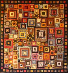"""jbe200quilts:    Africana 90"""" x 97""""  Nancy Neumann Pattern: log cabin variation Batting: Warm & Natural cotton Backing: Large central block is a cotton brown print called """"Emily's Memories"""" by Red Rooster Fabrics. Border is a coordinating cotton brown print called """"Cinnamon Stars"""" by Moda. Quilted by Rolinda Langham with an abstract geometric grid."""