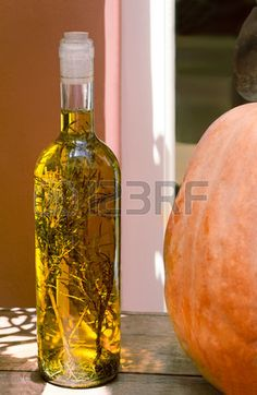 Still life on a wooden surface of the table is a bottle with olive oil and spices inside the bottle. It is next to the pumpkin.
