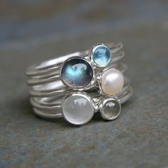 Moonlight on Water Stacking Rings Like moonlight on water, 5 sterling silver stacking rings with a lovely mix of luminous stones and pearl. 2 gray green blue flash labradorites, one 6mm and one 4mm. 1 luminous 6mm moonstone. 1 4mm Swiss blue topaz. 1 5mm white freshwater pearl These rings are made to order in your size. For more stacking rings: https://www.etsy.com/shop/KiraFerrer?section_id=13894026&ref=shopsection_leftnav_2 You may also like: https://www.etsy.com/shop/KiraFerrer?ref=sh...