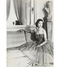 Hélène Rochas portant une robe de Marcel Rochas, au début des années 50, assise dans le grand salon de la rue Barbet de Jouy.