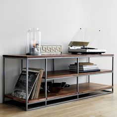 Shop framework credenza.   Architectural three-tier structure entertains in the raw.  Braced by sleek iron frame, wide planks of solid sustainable acacia wood show beautiful light-to-dark tones, active grain and naturally occurring knots.