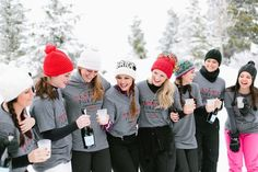 bridesmaids-in-the-snow-sipping-champagne-in-matching-shirts http://itgirlweddings.com/flannel-themed-bachelorette-party-weekend/