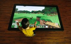 """Playing Minecraft on a Colossus gives gameplay a big boost. Look at the size of those controls! The Ultra HD resolution offers unmatched clarity, and the 84"""" display makes for a very immersive gaming experience.   Prequel video for Minecraft on one of our coffee tables can be found  here. Visit our website to find more about our multitouch tables and touch walls."""
