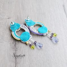 Hand embroidered soutache stud earrings with cream, purple and green. Made of soft soutache cord, crystal beads, Toho and Miyuki seed beads.  Lightweight.  Total length : 2.75 inch (7 cm) Widest part: 0.90 inch (2.3 cm)  Back covered in soft ultrasuede.  Matching bracelet: https://www.etsy.com/listing/198713834/ooak-soutache-bracelet-in-cream-white?ref=shop_home_active_13  To view the rest of my jewelry creations please visit : http://www.etsy.com/shop/Sengabeads  Each piece of Sengabeads…