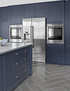 A wall of dark painted cabinets can be stark, but the soft, almost matte finish on the navy-blue doors and drawers in this handsome kitchen fades into the background, leaving the gleaming stainless-steel appliances to shine through.