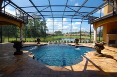 minimalist glass pool enclosure idea gold toned pavers for floors stone made water fountains luxurious screened pool of Create A Stylish & Functional Dip with These Ideas of Enclosed Swimming Pools