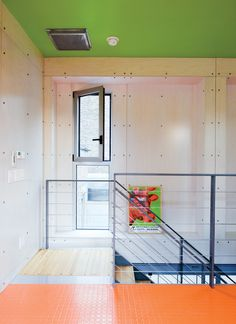 The entire house is marked by dramatic changes in color: Though the walls are white, the floors and ceiling swap tones, and pink fluorescent lights give way to a lavender bedroom ceiling. The domestic spectrum culminates in the orange floor and curtains of the rooftop penthouse—–proving that even diamond-plate steel and ventilation ducts, given some Safecoat paint, can be made as colorful and warm as a kindergarten.