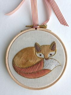 This cute Fox design, the second in the 'woodland creatures' series by Becky Hogg. The Fox is embroidered in 3 Metalwork techniques over layers of felt padding. Metalwork embroidery is a technique seen throughout history on pieces. The Fox has Antique Gold, Silver, and Copper metal threads in a variety of stitches including Couching, Chipping and Cutwork, all traditional skills in this beautiful style of embroidery. Measures approximately 8x6cm, and the wooden hoop is 11cm diameter.