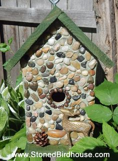 "Antelope Canyon Cedar birdhouse with front embellished with river rock collected from the lakes and shores of Lake Michigan and embellished with beautifully brass antelope, pinecone and beads.  Roof, sides, back and base is weatherproof stained in semi-transparent forest green colored 10 deck stain. Suitable for outdoor or indoor décor. Removable base for easy clean out.  12"" high X 8 3/4"" wide X 8 3/4"" deep       1 1/4"" opening  $70.00 plus $15 shipping"