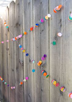 Store-bought tissue paper confetti, strung onto a garland with needle and thread...GREAT idea!! {100 Layer Cakelet}