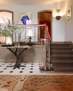 "Designer Katie Ridder's 1920's home.  ""The main serpentine staircase was given a lift with a red paint and silver leaf railing by artist Chuck Hettinger."""