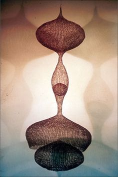 """Ruth Asawa, Untitled, S042, 1955. Hanging three continuous spheres with a hanging single sphere and small sphere in center middle sphere. Crocheted aluminum wire (36"""" diameter x 90"""" high)."""