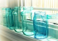 DIY seaglass mason jars are perfect for summer wedding decor. Simply mix food coloring with Elmer's glue, paint on, and let dry!