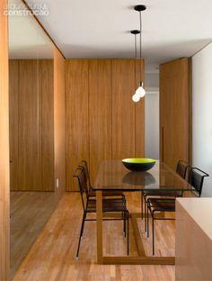 A porta pivotante da sala de jantar isola o corredor que dá acesso ao lavabo e à suíte do casal. Para conseguir uma sensação de profundidade, o arquiteto optou por aplicar um espelho de 2,50 x 2,50 m em parte do painel de freijó natural, que soma 8,50 x 2,50 m.