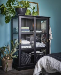 Grande vitrine entourée de plantes vertes et remplie de livres et de linge de lit.