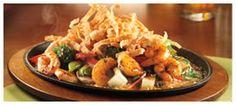 Sizzling Asian Shrimp: Deliciosos camarones a la plancha, servidos sobre una cama de sabroso arroz y una mezcla de vegetales asiáticos, acelga, brócoli, castañas de agua, porotos verdes, champiñones y zanahoarias. Bañados con una salsa agridulce y cubiertos con crujientes tiras de wonton y cilantro. Foto referencial.