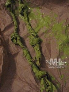 Cut the width of brown packing paper in half, then twist and tie a few knots. Green latex paint turns them into jungle vines.