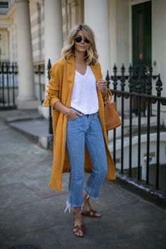 Emma Hill wears Mustard duster coat, cropped frayed jeans, Hermes Oran tan leather sandals, basic white t shirt, and a Simon Miller Bonsai bag .