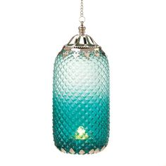 An exquisite diamond-patterned lantern steeped in decadent turquoise and encircled by sophisticated silver-toned filigree makes a worldly statement. Light a candle and watch the room twinkle with exotic flair.