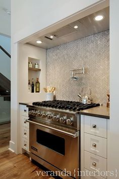 herringbone tile backsplash + range shelf nook in contemporary kitchen by veranda interiors