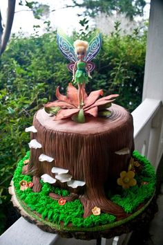 Tinkerbell on a tree stump Chocolate cake with vanilla buttercream covered in mmf. Gum paste flowers and mushrooms. Tink is a toy the bday girl wanted on her cake.: