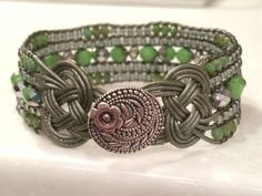 This lovely 5 row cuff bracelet is handcrafted with green and silver mix multi faceted beads in the center, next two rows have small silver lined