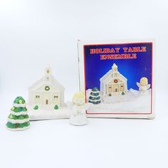 Vintage pre-owned bisque porcelain ceramic novelty three piece figural table ware set.  The set consists of a church shaped napkin holder and a Christmas tree and angel shaped salt and pepper shaker set.  The church shaped napkin holder has a square base with indentations for the shakers.  One shaker is shaped like a Christmas tree that is decorated with snow and the other shaker is a blonde girl angel in with her hands folded in prayer. #Vintage #Christmas #SaltAndPepperShakers