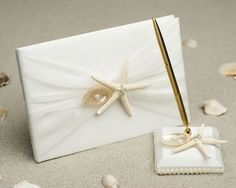 This cool beach wedding guest book and pen set is complemented with a delicate starfish and polished abalone shell. The abalone shell showcases a heart-shaped faux pearl accents, and the starfish showcases a rhinestone and faux pearl decor. This is a truly lovely piece that is sure to make a splash on your wedding day, especially for any destination weddings. Guest-book%...