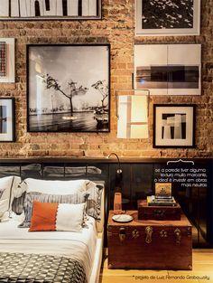 parede tijolo rústicom quadros, cabeceira alto brilho, baú como mesa de cabeceira, colcha geométrica