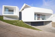 """Residential Architecture: J4 Houses by Vertice Arquitectos: """"..We were faced with a plot of land shaped as a quarter of a circumference that had a height difference of 5.50 meters on the curved side. This side has a privileged view of the sea. In addition, we were conditioned by the construction regulations which enabled us to build two terraced levels..The project is based upon two containers, which have been cut, in order to adopt a """"mineral"""" form. These different volumes have been designed..."""