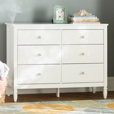 Make your child's room standout in the most elegant way with the Arinna 6-Drawer Dresser by Viv + Rae. Bright and glamorous, this dresser features chic subtle details such as turned wood feet, six elegant clear acrylic knobs and clean lines in a white finish, all of which are sure to make a fashion statement in your child's room. Designed with six spacious drawers, the Arinna includes two small drawers along the top and four larger bottom drawers. All drawers are equipped with wheel glides…