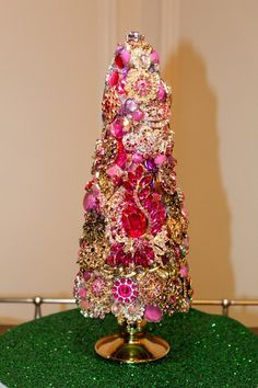 Elegantly handcrafted centerpiece tree. This unique one of a kind piece stands about 13 1/2 inches tall and is about 6 inches at the widest part. It is covered in approximately 75 beautiful brooches, crystals, rhinestones and pearls. These pieces unlike others, are totally encrusted in jewels. This
