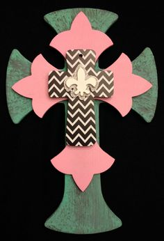 """Small wooden, triple layer, wall cross. Painted with turquoise and pink acrylic paint and topped with a black and white chevron patterned cross. The piece is then topped with a small silver glitter and white Fleur-de-lis. Dimensions are approximately 8"""" x 12"""". Each cross is handmade with love and truly one of a kind."""