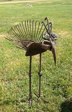 A rusty rake and spade - remade into a metal garden bird