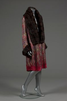 An opera coat, late 1920s, of printed floral silk brocaded in silver, with deep brown fur shawl collar and cuffs, the hem appliqued in rose velvet and studded with pastes, lined in gold lame Provenance: orginally the property of Lady Cornwallis.