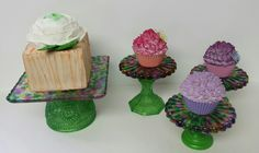 Hand made cake and cupcake stands. Tops made from melted pony beads and glued to 4in and 2in wooden candlestick holders that I painted with MS glass paint and acrylic paint. Faux Hydrangea cupcakes and faux flower top cake. Created by Sara Landin.